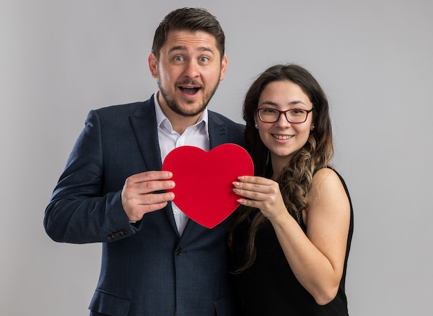 Jovem lindo casal feliz, homem e mulher segurando um coração vermelho, sorrindo alegremente, felizes e apaixonados juntos comemorando o dia dos namorados