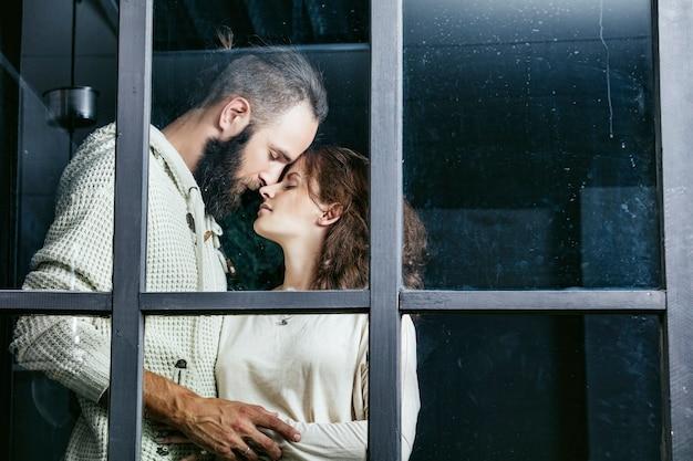 Jovem lindo casal heterossexual, homem e mulher, amantes se abraçando do lado de fora da janela