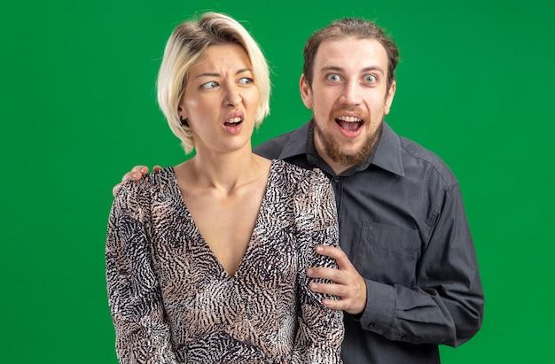 Jovem lindo casal homem e mulher feliz apaixonado homem feliz abraçando sua namorada confusa comemorando o dia dos namorados em pé sobre fundo verde
