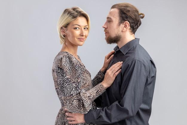Jovem lindo casal homem e mulher felizes apaixonados juntos celebrando o dia dos namorados em pé sobre uma parede branca