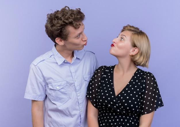 Jovem lindo casal homem e mulher felizes apaixonados, mantendo os lábios enquanto se beijam em pé sobre a parede azul