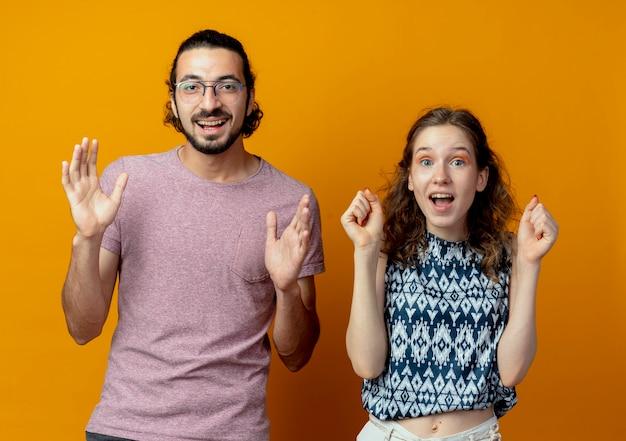 Jovem lindo casal homem e mulher felizes e animados, cerrando os punhos e levantando os braços em pé sobre a parede laranja