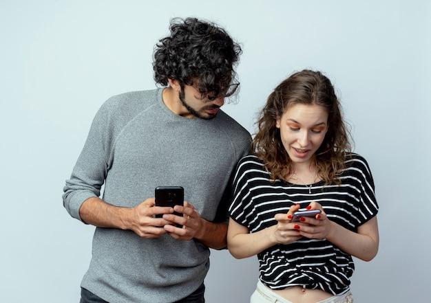 Jovem lindo casal homem e mulher, homem espiando e espiando o celular de sua namorada sobre uma parede branca