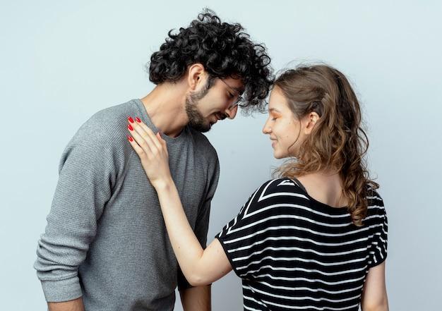 Jovem lindo casal homem e mulher tocando o ombro de seu namorado feliz e apaixonado em pé sobre uma parede branca