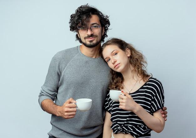 Jovem lindo casal homem e mulheres felizes no amor segurando xícaras de café, sentindo emoções positivas sobre a parede branca