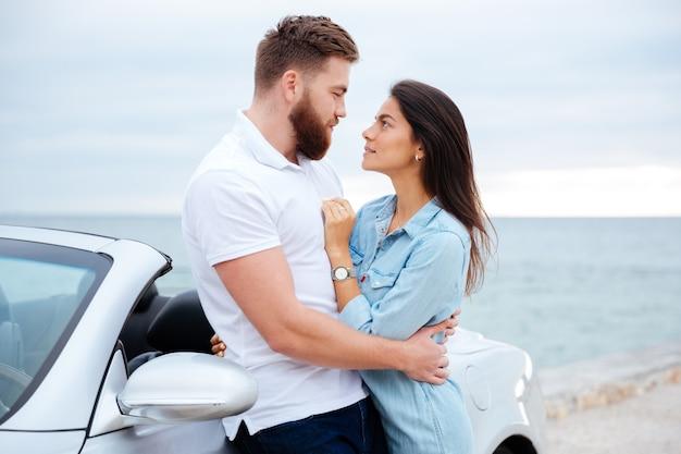 Jovem lindo casal jovem se abraçando em pé perto do carro à beira-mar