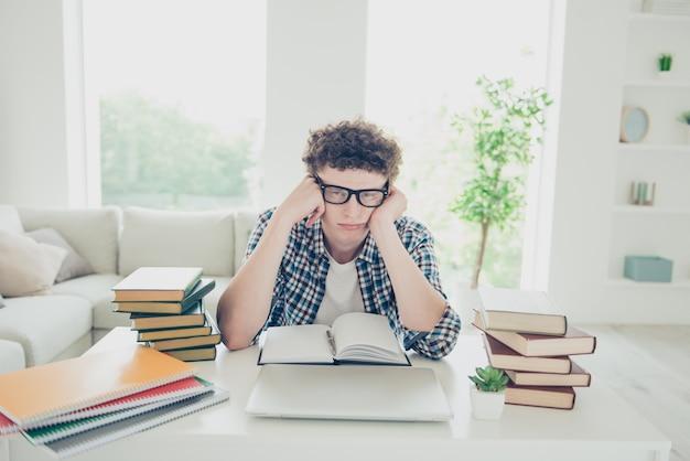 Jovem lindo e cansado em casa nerd de óculos estudando