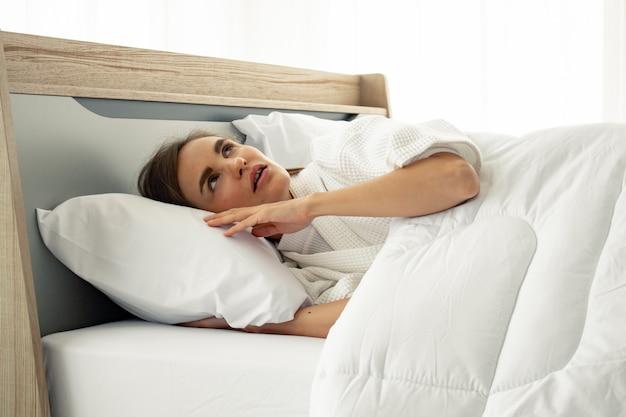 Jovem lindo sono na cama em casa.