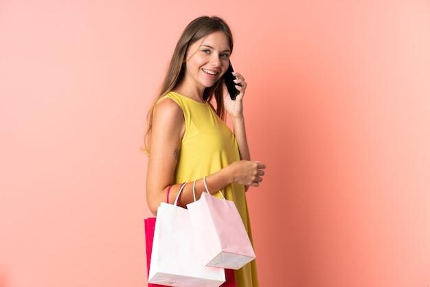 Jovem lituana isolada em um fundo rosa segurando sacolas de compras e ligando para um amigo com o celular