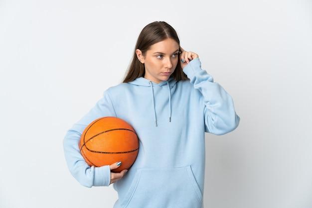 Jovem lituana jogando basquete, isolada no fundo branco, tendo dúvidas e pensando