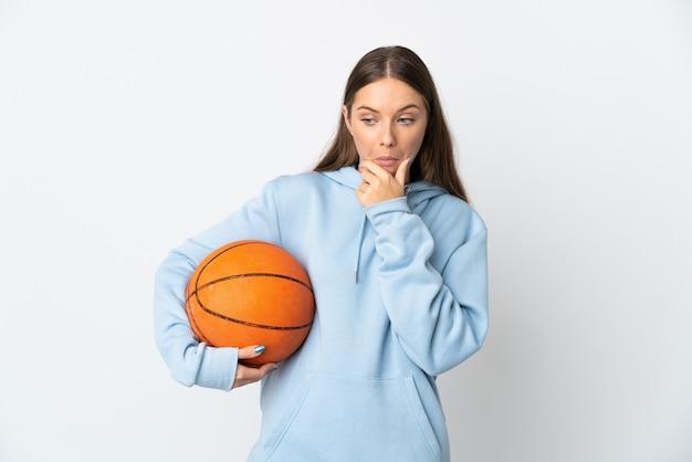 Jovem lituana jogando basquete, isolada no fundo branco, tendo dúvidas
