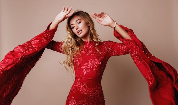 Jovem loira adorável vestido vermelho luxuoso com mangas largas. pose expressiva.