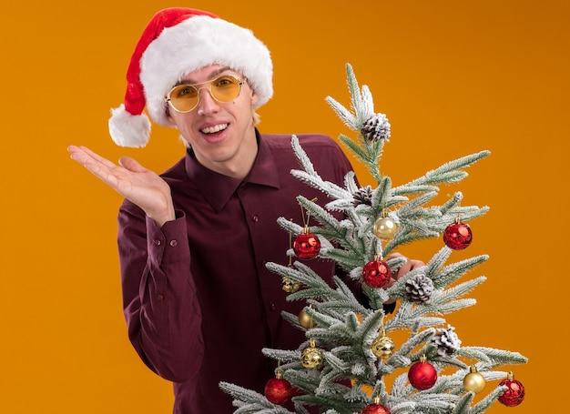 Jovem loira alegre com chapéu de papai noel e óculos, atrás de uma árvore de natal decorada, mostrando a mão vazia isolada na parede laranja