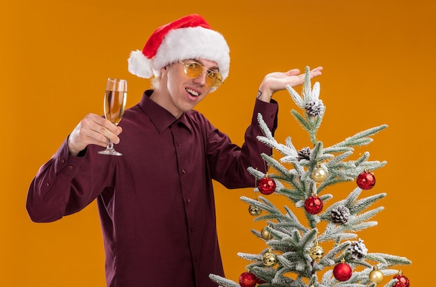 Jovem loira alegre com chapéu de papai noel e óculos em pé perto de uma árvore de natal decorada, apontando para ela segurando uma taça de champanhe, olhando para a câmera isolada em um fundo laranja