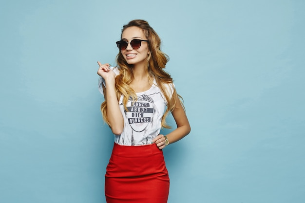 Jovem loira alegre em camiseta branca, saia vermelha e óculos de sol sorrindo e posando