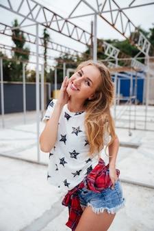 Jovem loira alegre posando ao ar livre