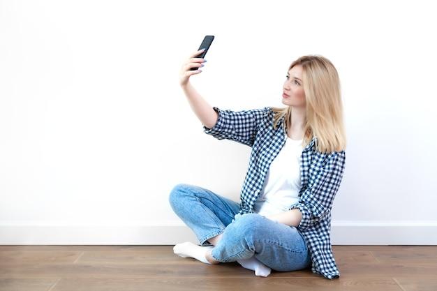 Jovem loira alegre tirando selfie com smartphone preto