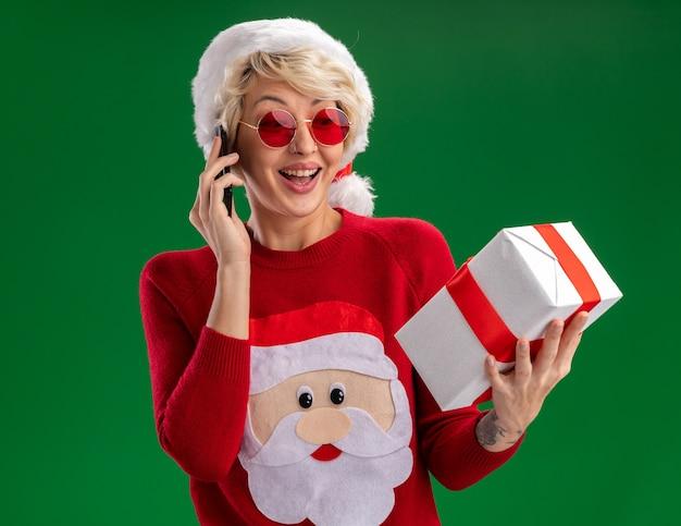Jovem loira alegre usando chapéu de natal e suéter de natal de papai noel com óculos segurando e olhando para um pacote de presente falando no telefone isolado na parede verde