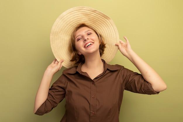 Jovem loira alegre usando um chapéu de praia, agarrando um chapéu isolado na parede verde oliva