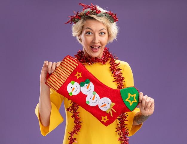 Jovem loira animada com coroa de flores de natal e guirlanda de ouropel no pescoço, segurando uma meia de natal, olhando para a câmera isolada no fundo roxo