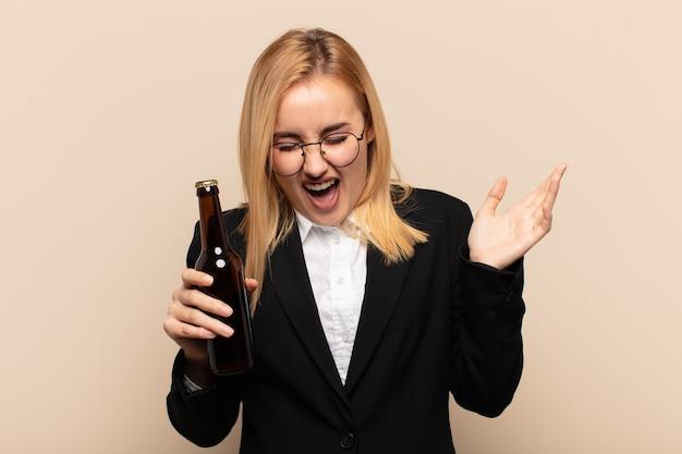 Jovem loira animada com uma cerveja