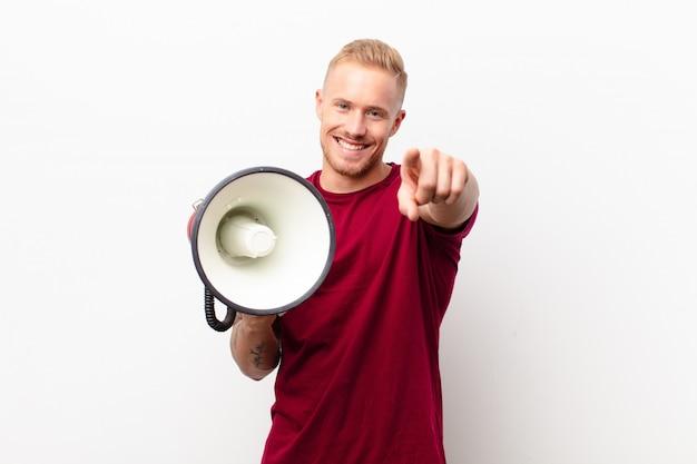 Jovem loira apontando com o dedo contra uma parede branca com um megafone