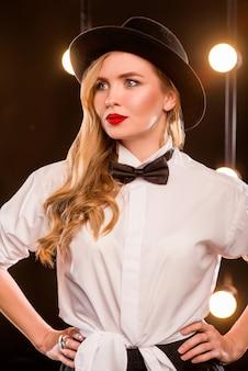 Jovem loira atraente com camisa branca borboleta chapéu preto em fundo escuro