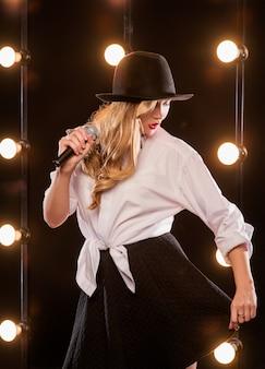 Jovem loira atraente com camisa branca e chapéu preto borboleta com microfone cantando no palco