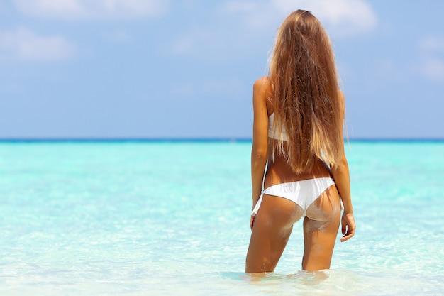 Jovem loira atraente com corpo esportivo perfeito de biquíni na praia tropical de verão
