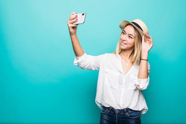 Jovem loira atraente e alegre está sorrindo, tirando uma selfie do telefone, vestindo uma roupa casual de verão e um chapéu na parede azul