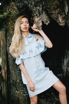 Jovem loira atraente em um vestido azul posando com uma árvore velha