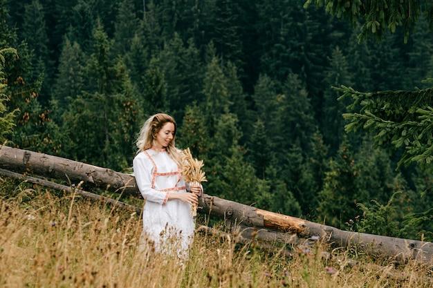 Jovem loira atraente em um vestido branco com bordado posando com buquê de espigas em uma paisagem pitoresca.