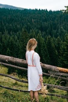 Jovem loira atraente em um vestido branco com bordado posando com buquê de espigas perto de uma cerca de madeira sobre uma paisagem pitoresca
