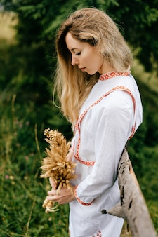 Jovem loira atraente em um vestido branco com bordado posando com buquê de espigas perto de uma cerca de madeira