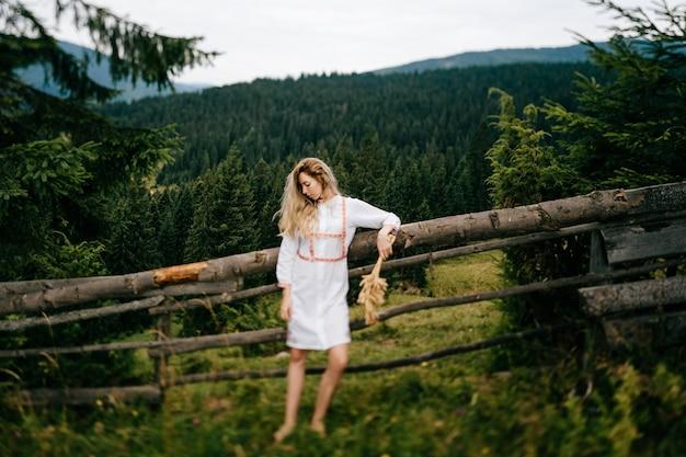 Jovem loira atraente em um vestido branco com bordado posando com um buquê de espigas perto de uma cerca de madeira