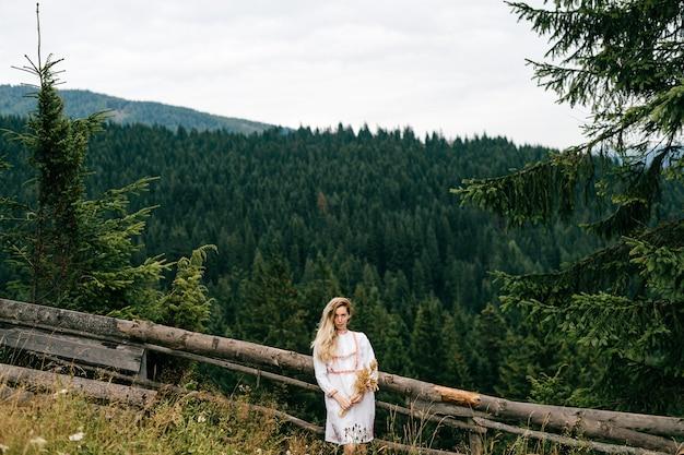 Jovem loira atraente em um vestido branco com bordado posando com um buquê de espigas sobre uma paisagem pitoresca