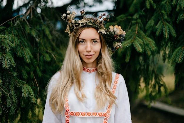 Jovem loira atraente em um vestido branco com enfeite e guirlanda de flores na cabeça posando sobre galhos de pinheiro.