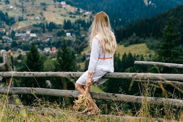 Jovem loira atraente em um vestido branco com enfeite sentado na cerca de madeira com buquê de espigas sobre a pitoresca paisagem campestre