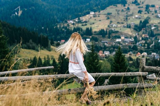 Jovem loira atraente em um vestido branco com enfeite sentado na cerca de madeira com buquê de espigas sobre a pitoresca paisagem rural