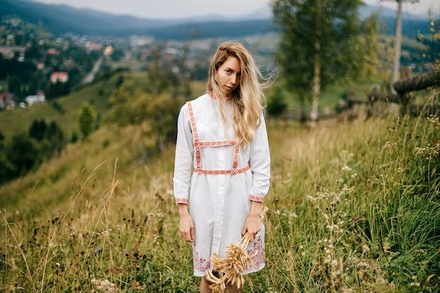 Jovem loira atraente em um vestido branco com ornamento posando com buquê de espigas em uma paisagem campestre pitoresca