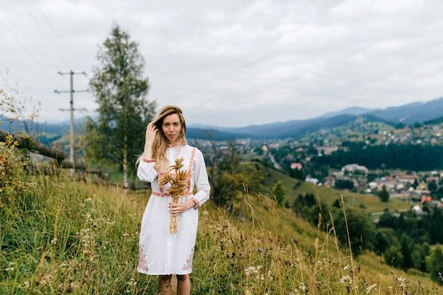 Jovem loira atraente em um vestido branco com ornamento posando com buquê de espigas sobre a pitoresca paisagem rural