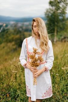 Jovem loira atraente em um vestido branco com ornamento posando com buquê de espigas sobre o fundo do campo
