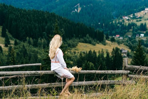 Jovem loira atraente em um vestido branco com ornamento sentado na cerca de madeira com buquê de espigas sobre a pitoresca paisagem