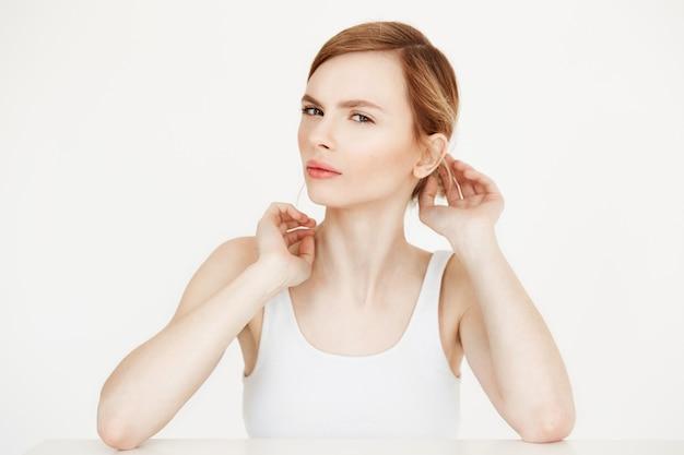 Jovem loira bonita com a pele limpa, fresca, sentado à mesa, corrigindo o penteado. beleza e spa.