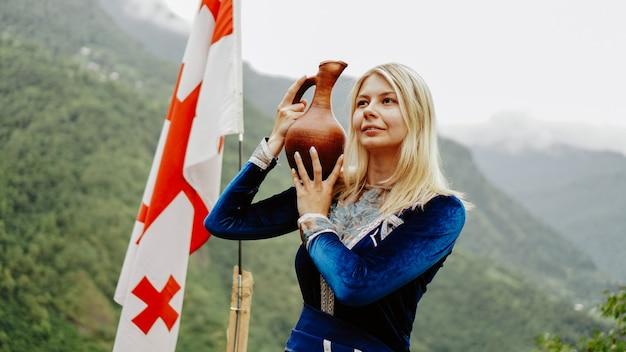 Jovem loira bonita com roupas da geórgia no contexto da bandeira da geórgia e as montanhas