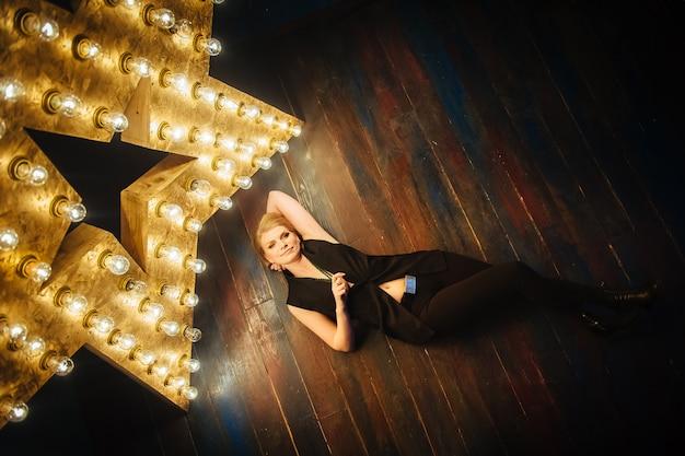 Jovem loira bonita de preto encontra-se no chão de madeira no fundo de uma estrela.