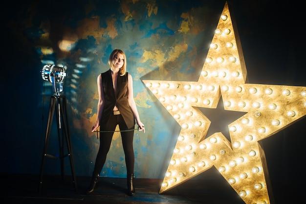 Jovem loira bonita fica no fundo de uma grande estrela com lâmpadas.