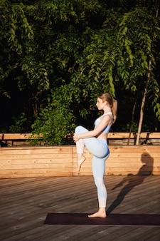 Jovem loira bonita praticando ioga fora ao nascer do sol.