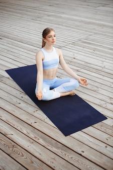 Jovem loira bonita praticando ioga fora.