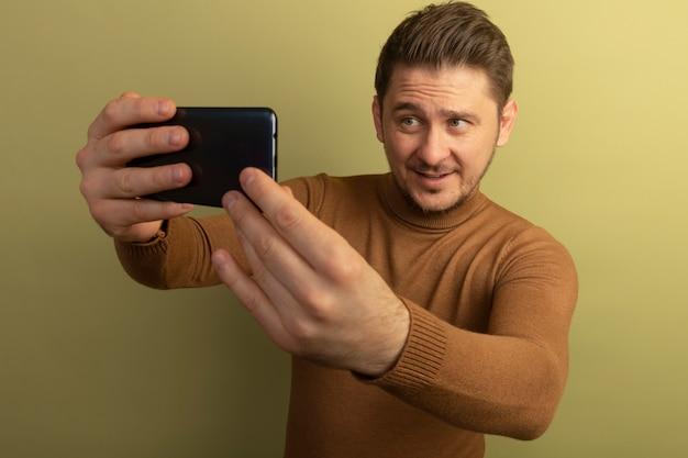 Jovem loira bonita satisfeita tirando uma selfie isolada na parede verde oliva